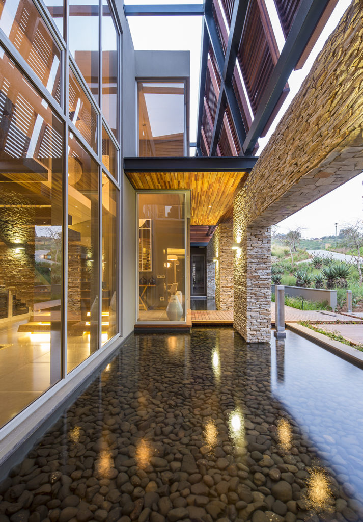 Just outside the main entry, we see a stone-bottom pond that flanks the wooden entry bridge, overlooked by massive glass panels on the home. Above, wooden louvered panels grant privacy and shade to the upper levels.