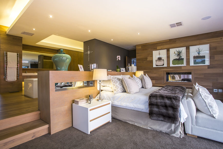 The master bedroom is a luxurious suite, combining several major elements over a layered floor plan. The bed area sits lowest, near sliding glass doors that access the balcony, while an en suite bathroom sits on a raised wood area.