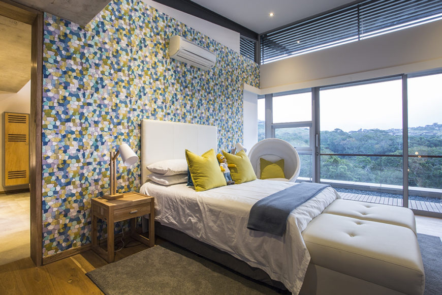Here's a secondary bedroom, awash in bright colors thanks to a patterned feature wall. To the right, we can see the full height glass sliding panels that allow for breathtaking views and direct balcony access.