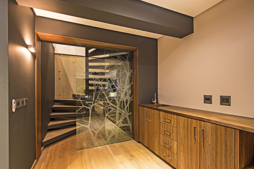 Moving to the lower level of the house, we see more hardwood flooring, natural wood cabinetry, and an intriguing glass divider wall with laser etched tree designs.