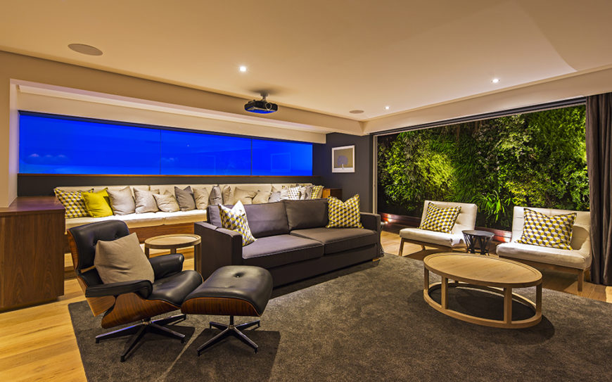 On this level we see another large living room space, with a lengthy sectional against the back wall and set of midcentury modern chairs in the foreground. To the right, another vast window offers views of the environment.