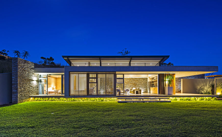 Seen from across the back lawn, the home positively glows from within. We can see right through to the interior, courtesy of those massive glass panels.