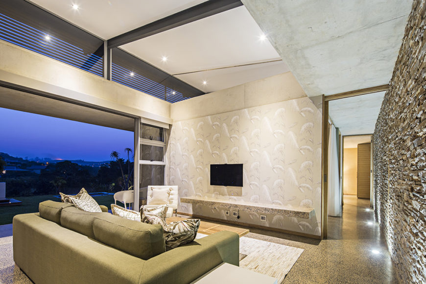 Within the numerous private and social spaces of the home, we see direct and broad access to the outdoors via sliding glass panels. Here, a stone wall connects all of the various rooms in the open plan design.