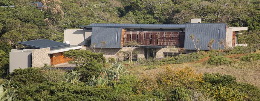 From a distance, we can see the intricate layering of the home's construction, with an angled steel roof raised above the stone and natural wood structure.