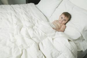 Baby sleeping under down blanket