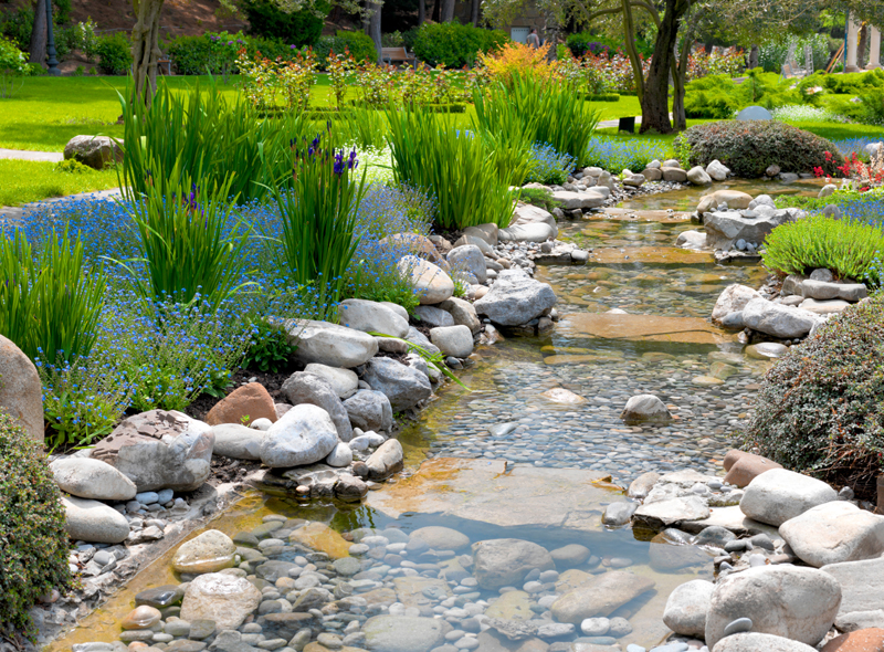 This delightful garden with pond in Asian style is inviting anyone passing by to stop and enjoy skipping some rocks, dipping their toes in, or just simply taking a break to take all this beauty in.