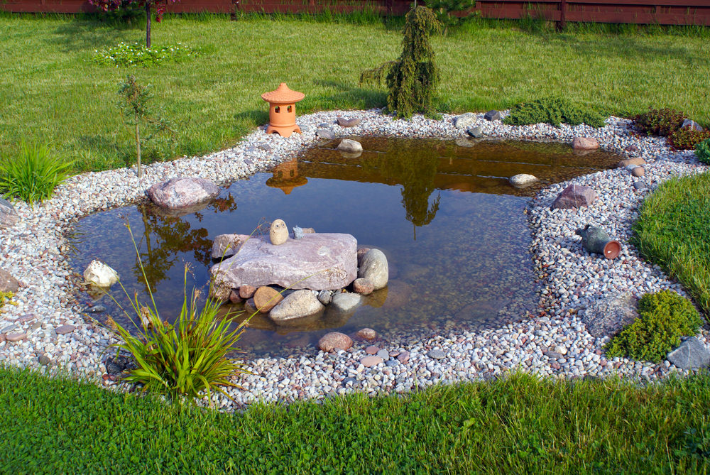A shallow pond decorated with small colorful rocks and a terracotta lantern, give an Asian flair to this area of the yard.