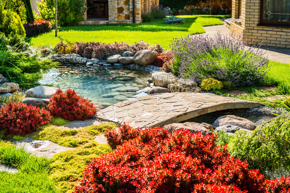 A beautiful and peaceful oasis, this garden pond brings together lots of colorful plants and a cool rock bridge, all with an Asian flair. LOVE it!