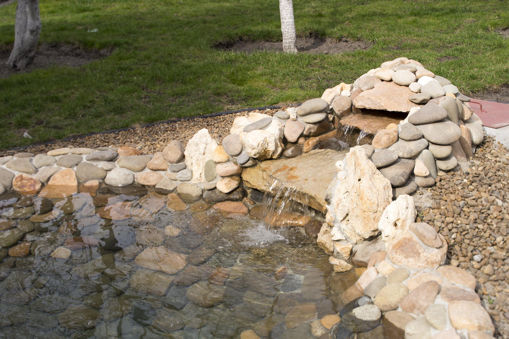 Layered rock waterfall gives this simple pond just what it needs to soothe and invite recreation. Easy to maintain, this might be one of the easiest ponds to create. Perfect for beginners!