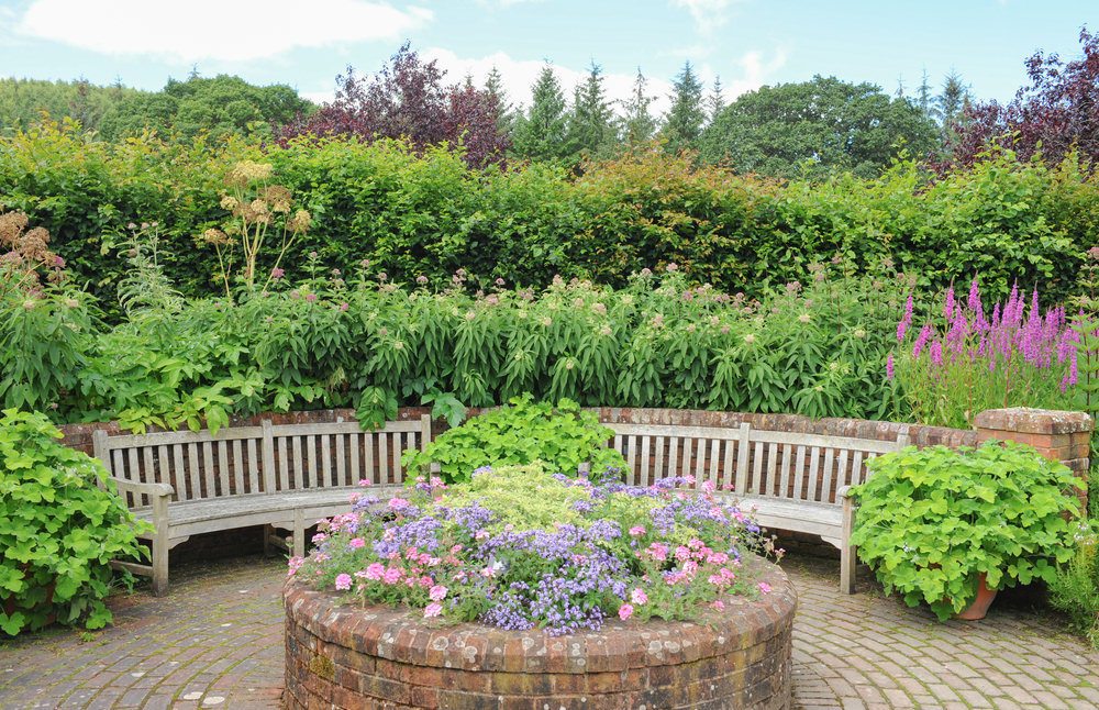 Nothing is as charming as a brick flower garden that is overflowing with pastel colored flowers. Who wouldn't want to take a break on the benches and admire the peace and quiet while admiring this quaint little garden?