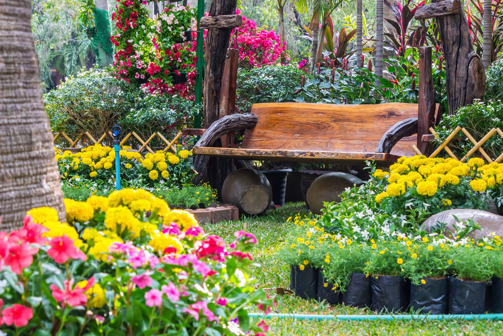 Sit like a queen on this wooden bench garden surrounded with yellow and pink blossoms.