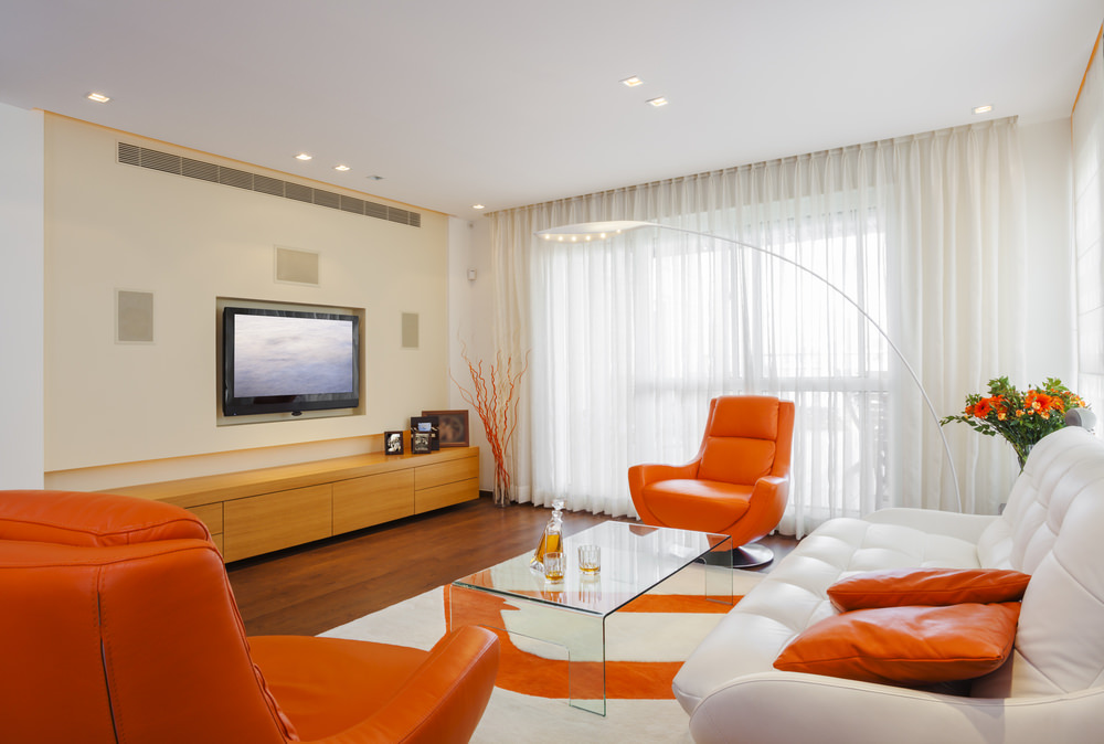 The fancy leather chairs and throw pillows in orange are stunning against the white background. The orange accented white floor rug displays a matching color scheme on the floor. The decorations on the center table, as well as the blossoms and twigs in the corners, are also orange.