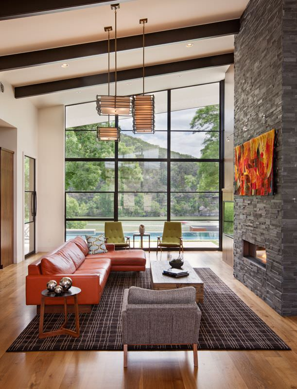 What looks more stunning in orange - the colorful and striking artwork on the brick stone fireplace or the leather sofa set? These two pieces highlight the room and give it a lively tone. The bright daylight coming from the glass wall helps a lot to keep the living room well lit.