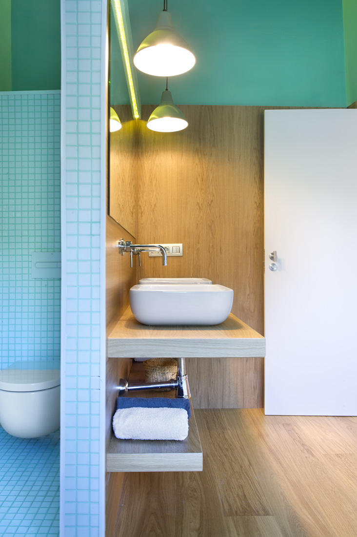 Pendant lamps lighten up the bathroom showing how smooth the wooded floor to wall texture is.