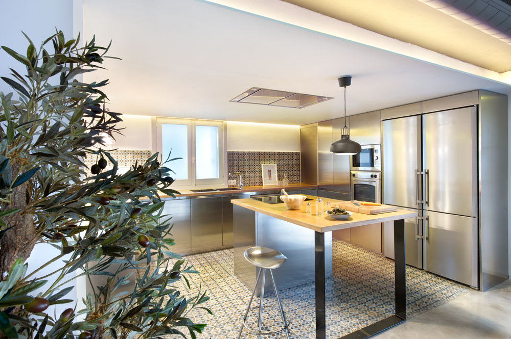 This is the stainless steel kitchen with steel kitchen counter bottom support and wooden top, steel cabinet doors, and high rise stool.
