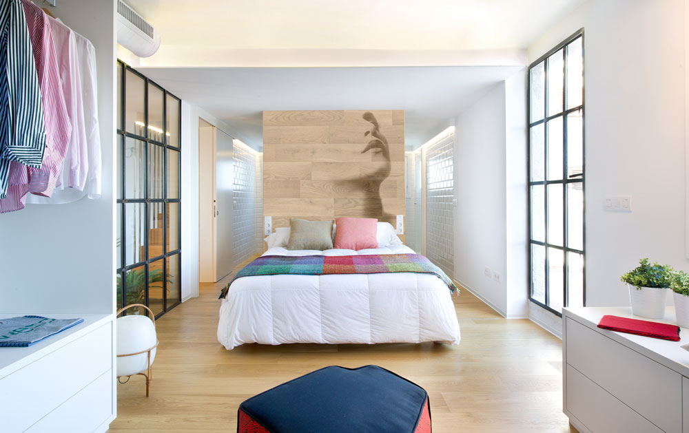 Most Asian inspired designs love artsy backdrops. A stylish wooden backdrop serves as a decorative headboard that matches the wood flooring.