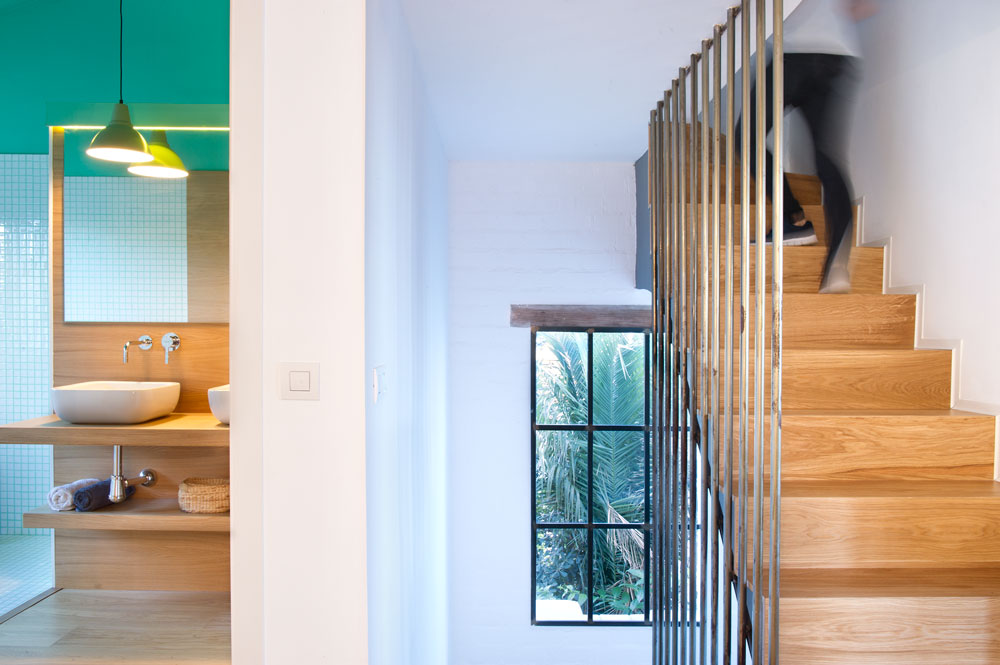 Opposite the wooden staircase is the bathroom. Peeking on its entrance is the wooden sink counter with a mirror, a pendant lamp and shelf underneath it.