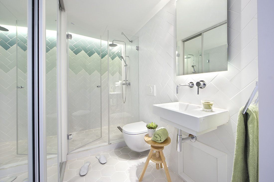 The neat and tidy bathroom looks even more spacious with the color shade choices and the sliding glass doors as well.