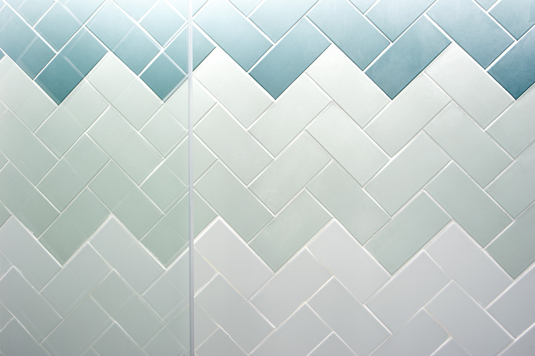 Fading from dark to light blue tile patterns in herringbone laying patterns.
