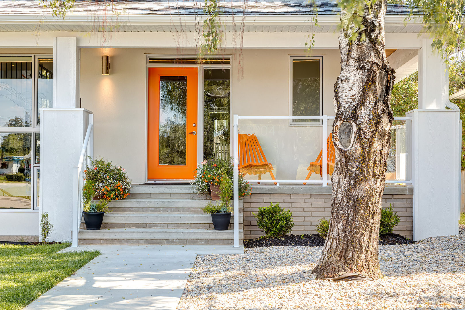 A front yard with concrete pathway ornamented with white pebbles and grass on each side, potted flowers and greenery on the steps. Orange coating on the glass front door and a pair of orange wooded chairs will approach you as you reach the front porch.