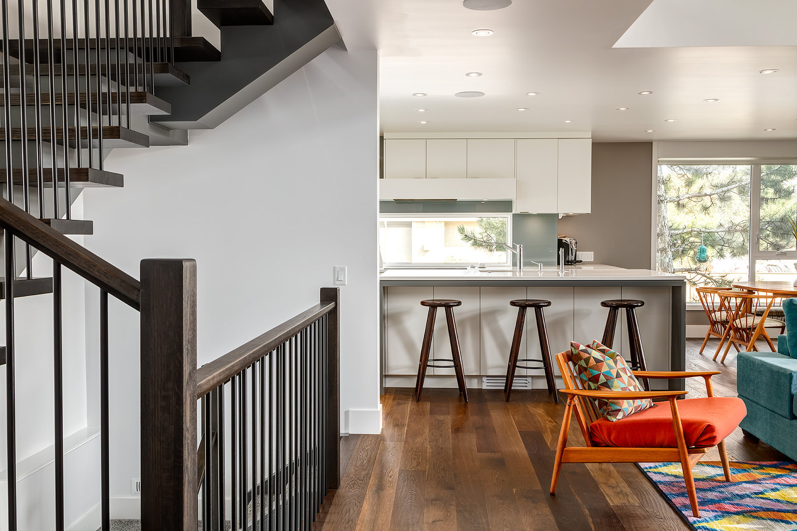 The open floor concept revealing the interconnected kitchen, dining and living area. The kitchen is made of plain and very minimalist designs with touches of wooden bar stools, the staircase railing is made of hard wood, while the living area is designed in a most lively tone.
