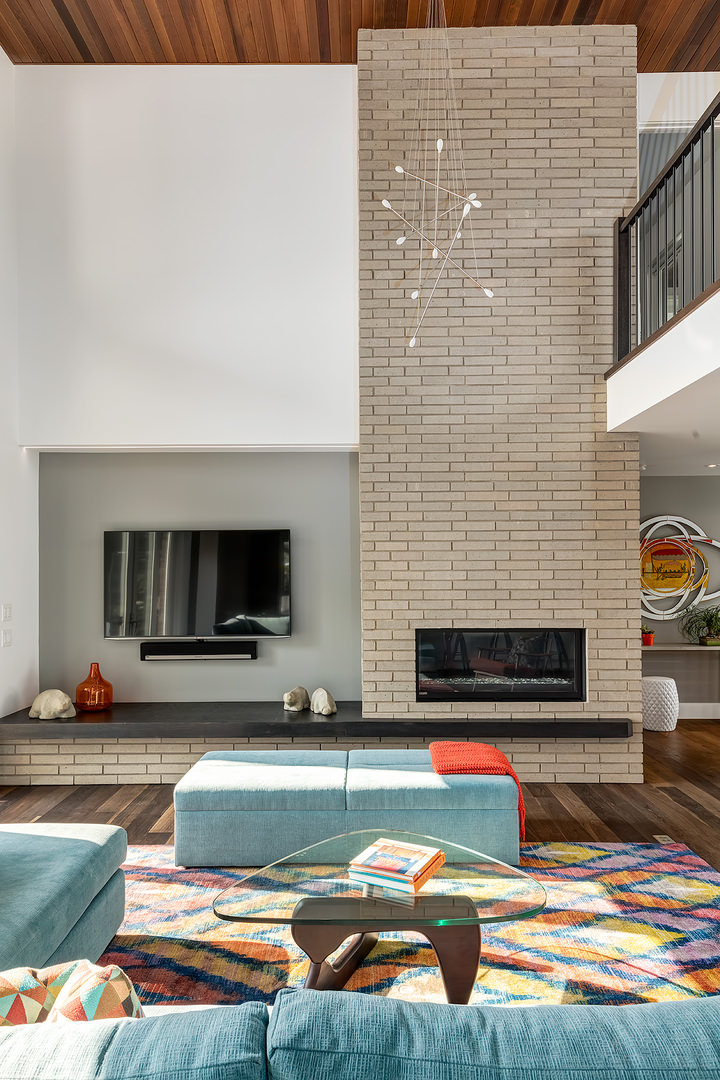 The very energetic and colorful tone of living area is quite visible in its floor rug, sofa and throw pillows. The unique design of the center table with glass top that resembles a guitar pick. The brick stone wall stretches from the main floor up to the second floor.