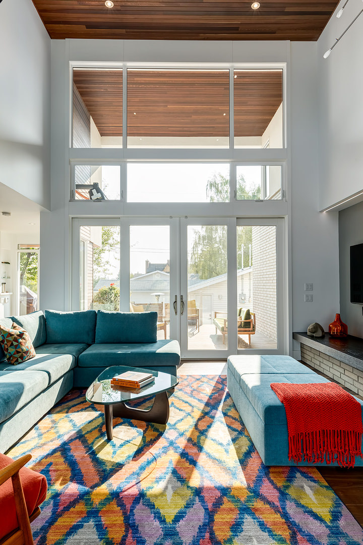 The wide and tall glass wall from floor to ceiling illuminates the entire living space with bright natural day light while the colors on the rug and furnishing get even livelier when strike by the light.