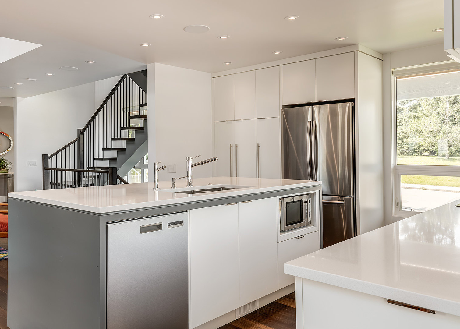 A few steel kitchen tools and equipment is incorporated in this kitchen giving it a shimmering touch and contrast in its pure white tone design.