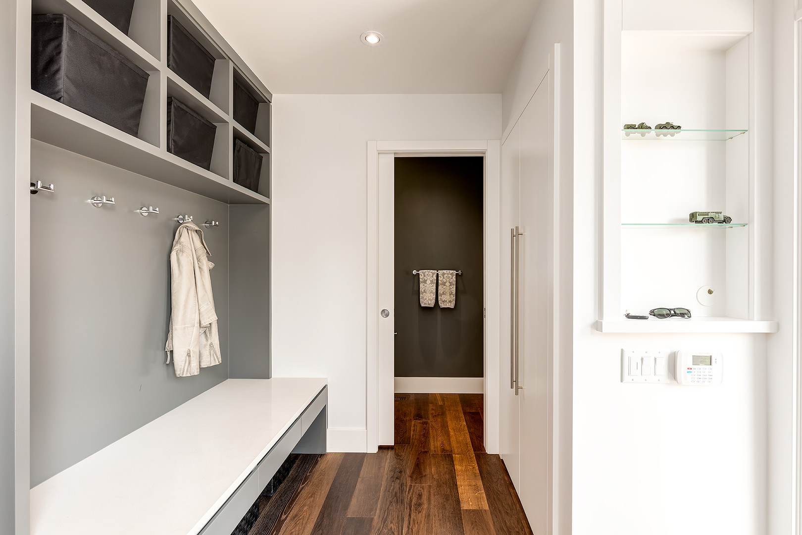 This is a walk through closet where you can hide all your coats and jackets. The floor is in glossy wood finish, a white, wide and lengthy folding counter on the side is present, storage and cabinets are provided for your clothing.