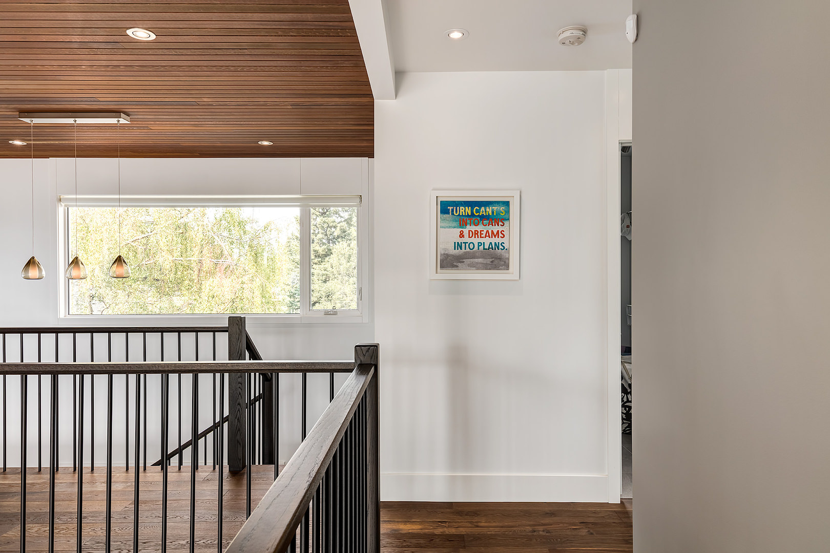 A single mounted frame catches the attention when you approach the staircase. The wall is finished in white stucco while the floor and ceiling are in tongue and groove cedar.