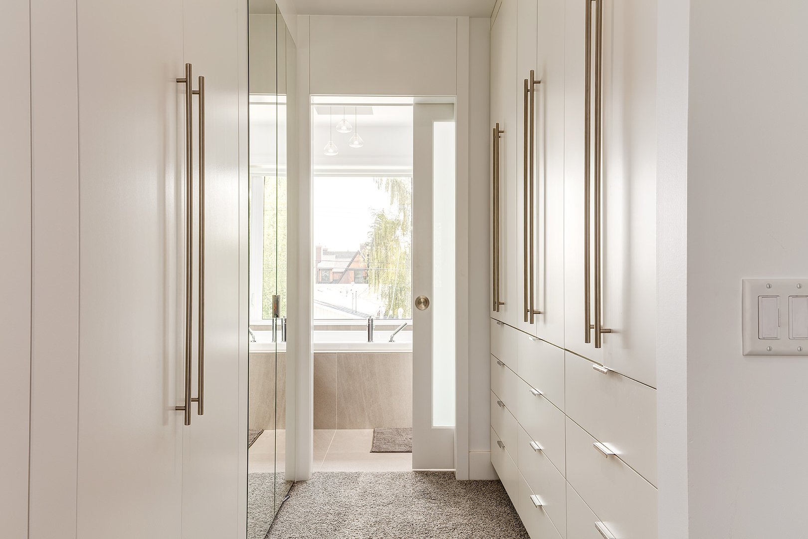 This hallway is entirely white and bright with white floor to ceiling cabinet on both sides, contrasting grey textured rug on the floor and glass door on the end.