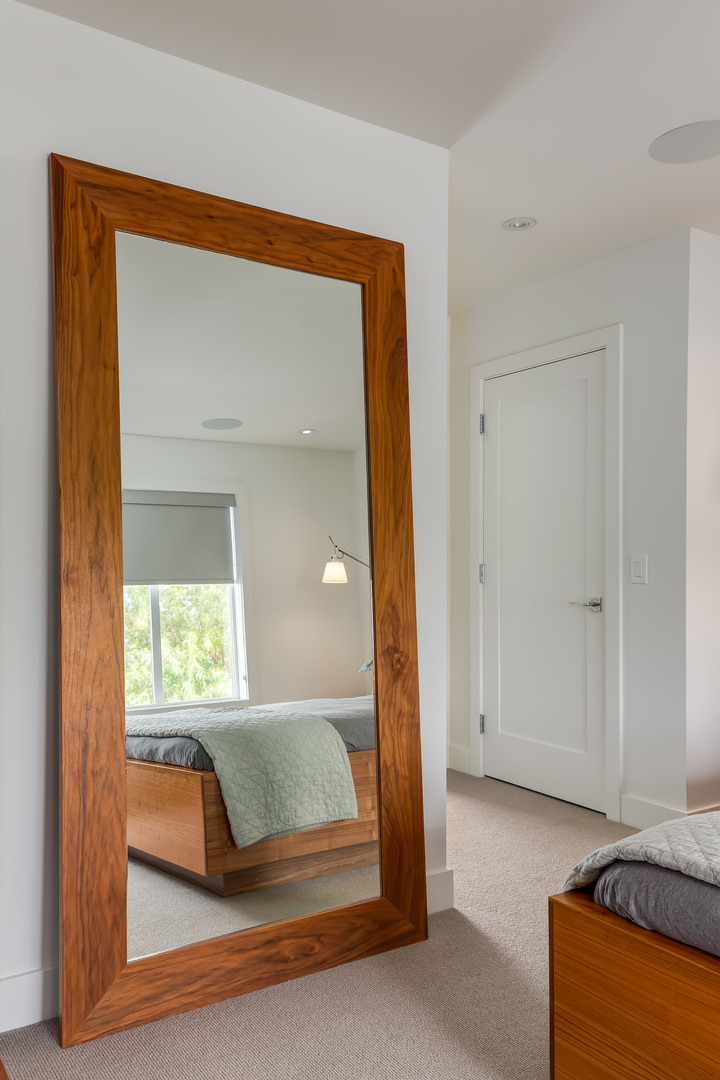 An almost floor to ceiling mirror, captured in a wooden frame provides an optical illusion of additional space in the room.
