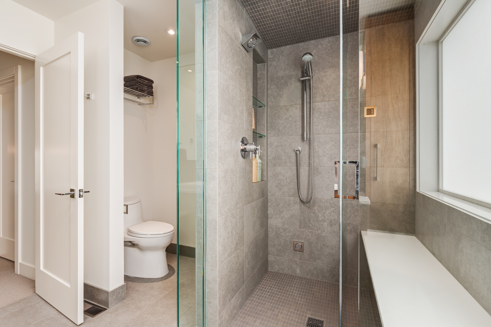A walk in shower with grey tiles mirrors the feel of the rest of the home, with contemporary chrome fixtures.
