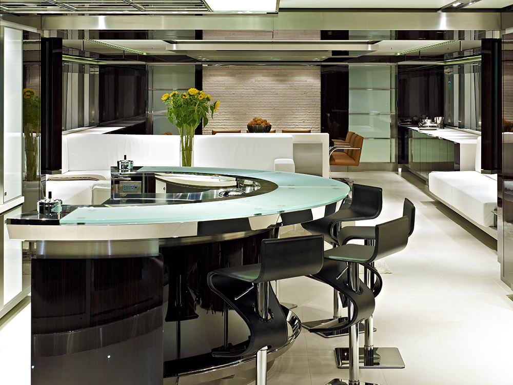 Another star of this yacht's interior is the ergonomic bar area with customized glass table in arched form. While the black leather bar stools are classy and chic, the white leather sofa itself serves as the divider between the living and bar area. The rough and unsmoothen limestone texture provides a rugged look of the dining area.