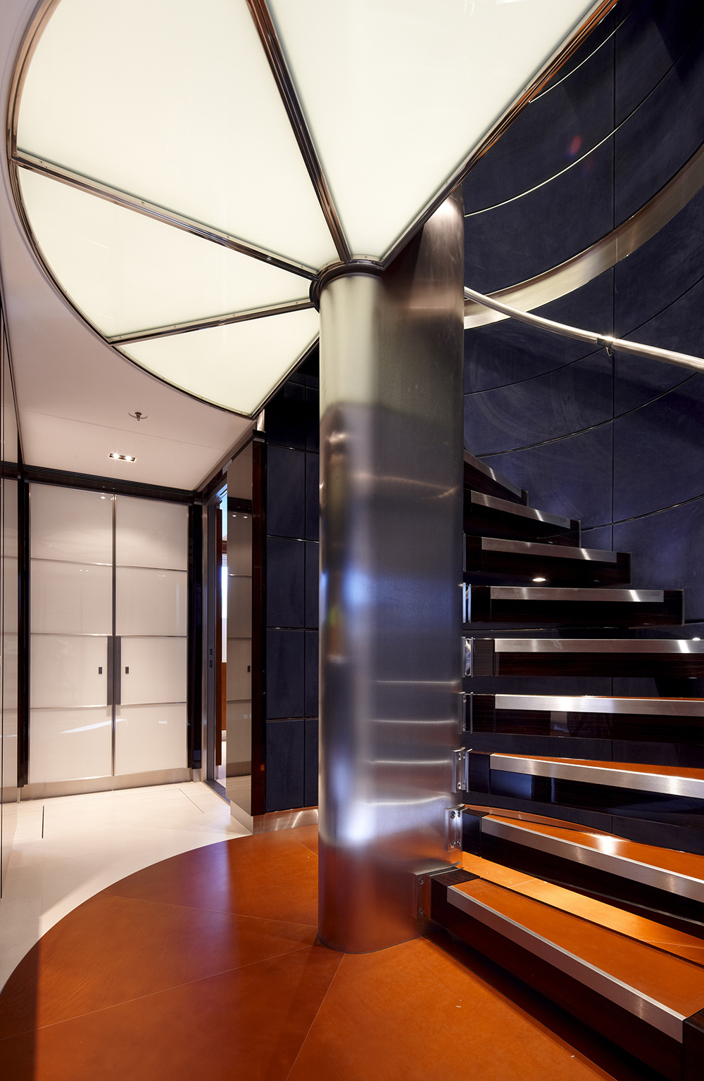 Geometry composed this area with lighted ceiling outlined with gleaming steels. The steel post support on the staircase glows with the steps steel outlines and hand railing. While matte finish flooring and steps' surface contrast the glowing effect.