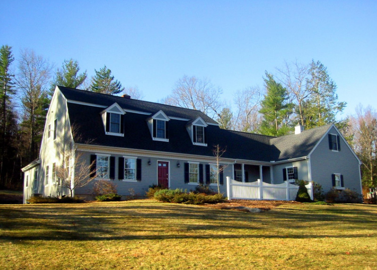 Main home has gambrel roof and attached garage has gable roof.