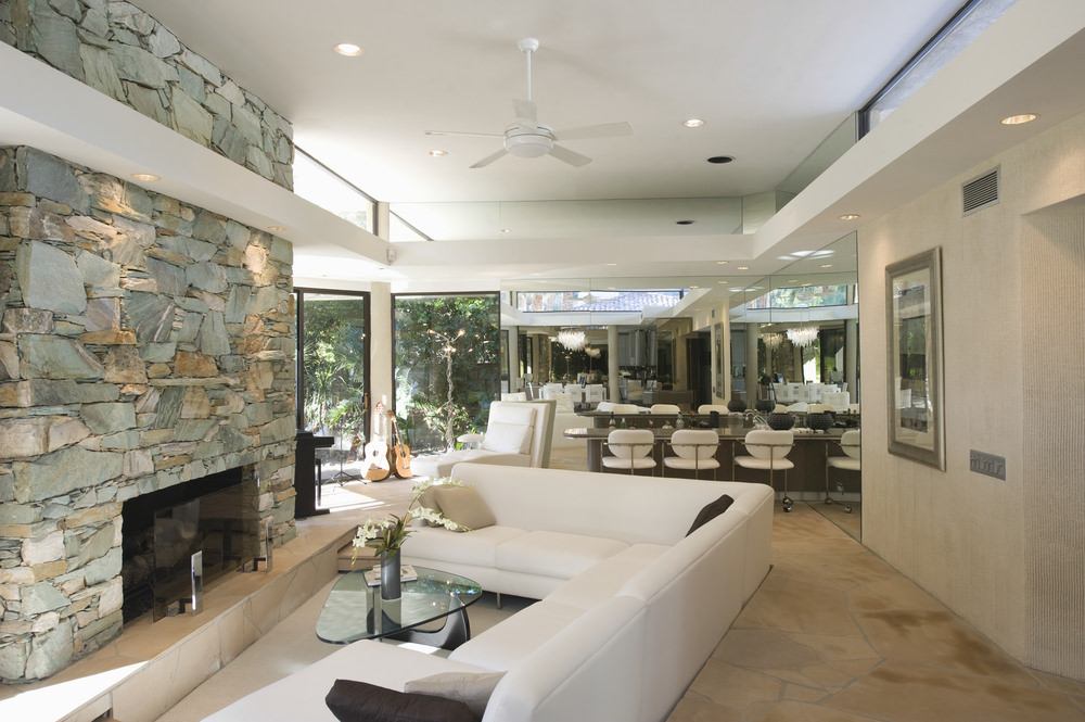 the white angled sectional sofa facing the stone fireplace is neat and sleek it adds - Nice Living Rooms