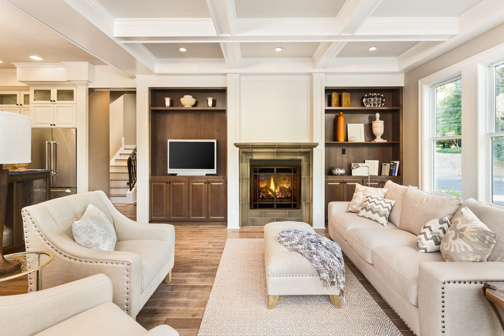 The coffered white ceiling is matched with a cream-colored sofa set with patterned throw pillows on it. The walls have built in wooden cabinets and shelves, while the floor has a glossy wood finish.