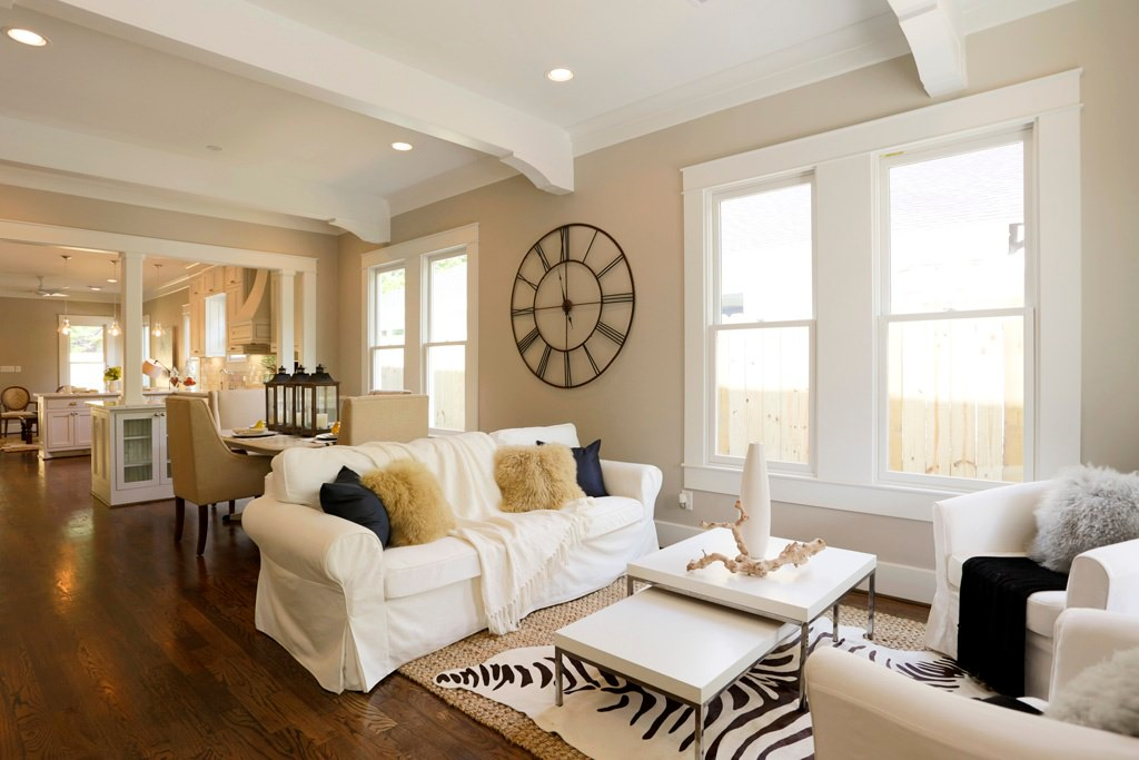 White covered sofa set and center table in an open concept house. Spreading on the wooden floor is a hand knit zebra print rug.