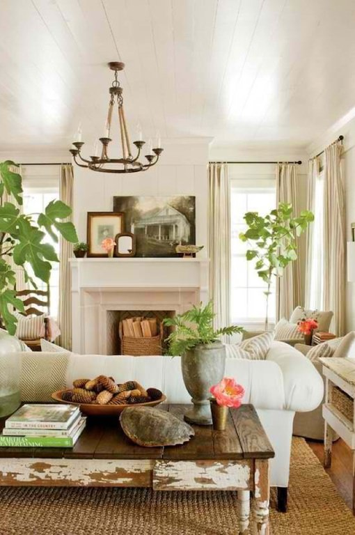 This looks like a farm house living room with rustic wooden desks, an antique vase, a knitted floor rug, a few hand knit baskets, and natural indoor greenery. The white sofa occupies the center space.