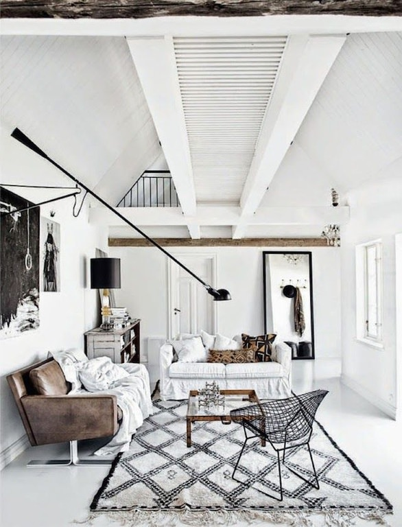 This living room looks slightly rustic but still cool; the combination of white and black is always beautiful. The leather sofa is covered with white cloth while the white floor is spread with a patterned floor rug.