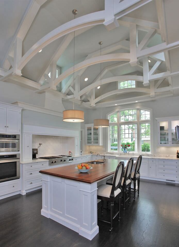 Soaring white spacious kitchen with a double wall oven next to the stove nook.