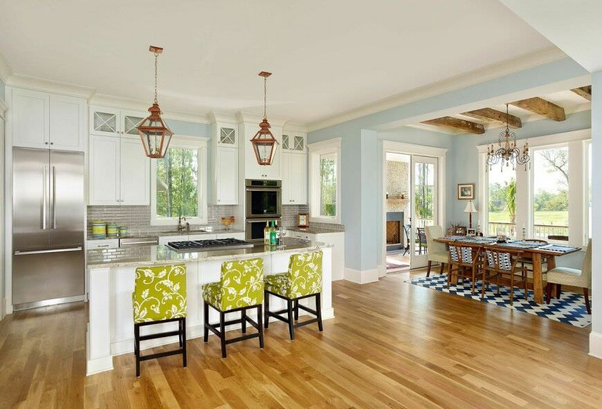 Spacious bright kitchen with subway tile backsplash and double wall oven flanking the sink.
