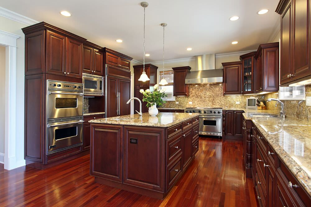 Massive kitchen with rich red wood floor, granite countertops and stainless steel double wall oven.