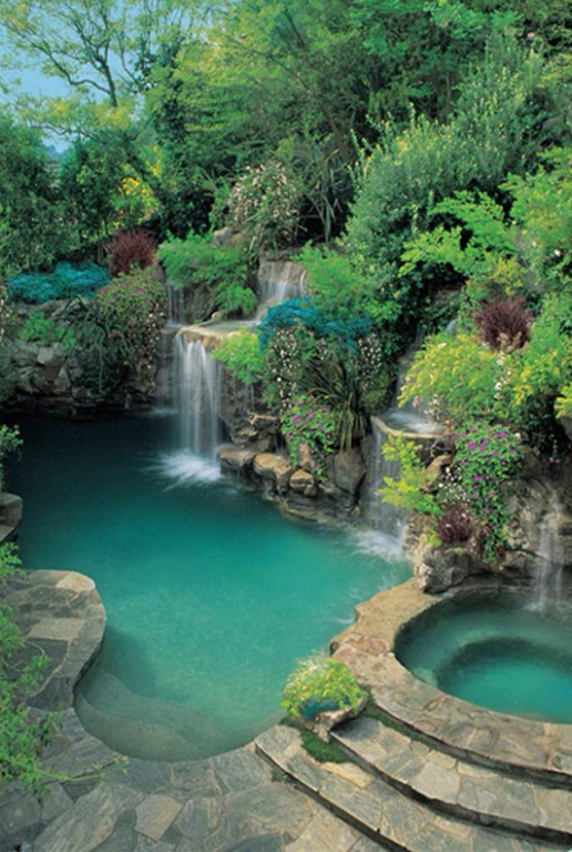 Luxurious freeform kidney-shaped swimming pool with waterfall and hot tub. This pool is all the more spectacular with the surrounding trees, bushes and flowers that terrace upward creating a private swimming oasis.