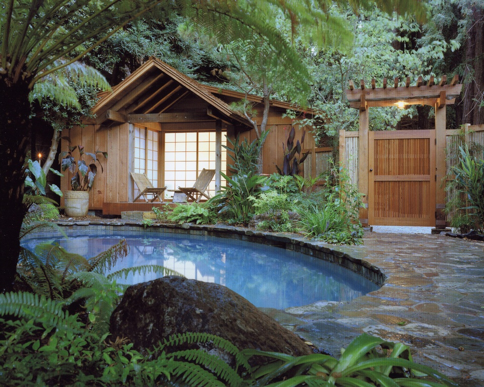 Here's a great example of an Asian-inspired backyard with Asian-designed poolhouse and gardens surrounding a small kidney-shaped pool.