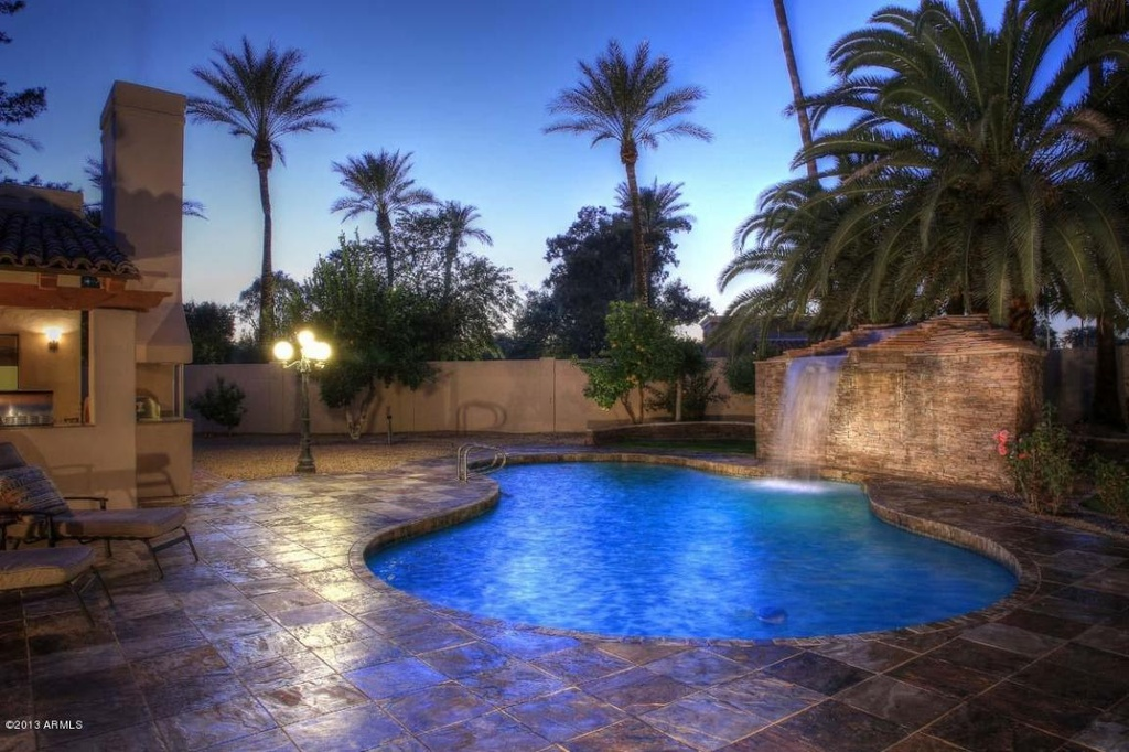 Dramatic kidney pool at night with crisp blue water and waterfall.