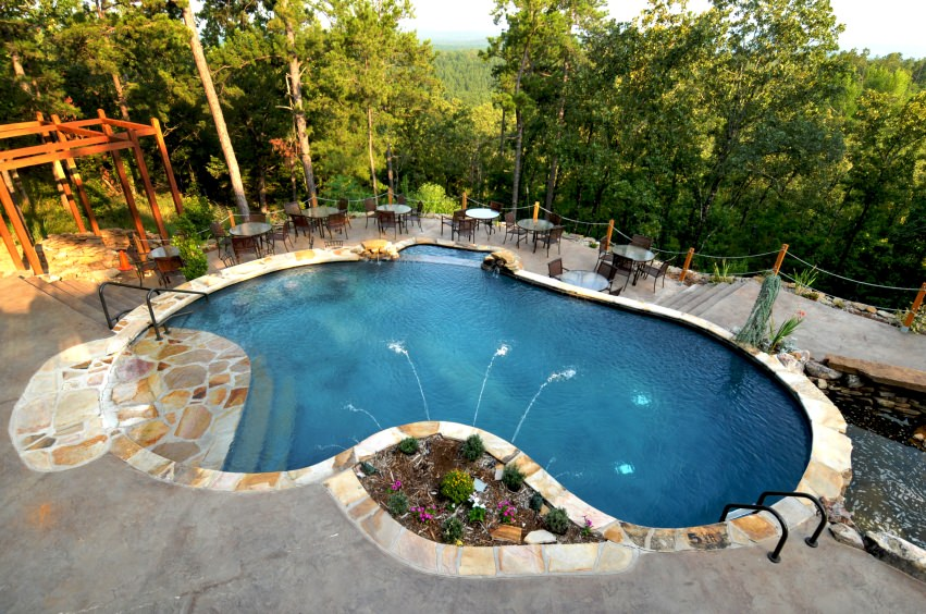 Large kidney shaped pool on the edge of a cliff overlooking the forest.
