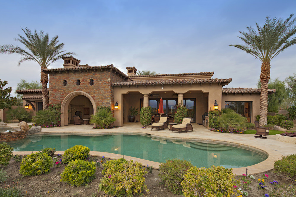 Kidney pool surrounded by patio and gardens in the backyard of a Tuscan style home.