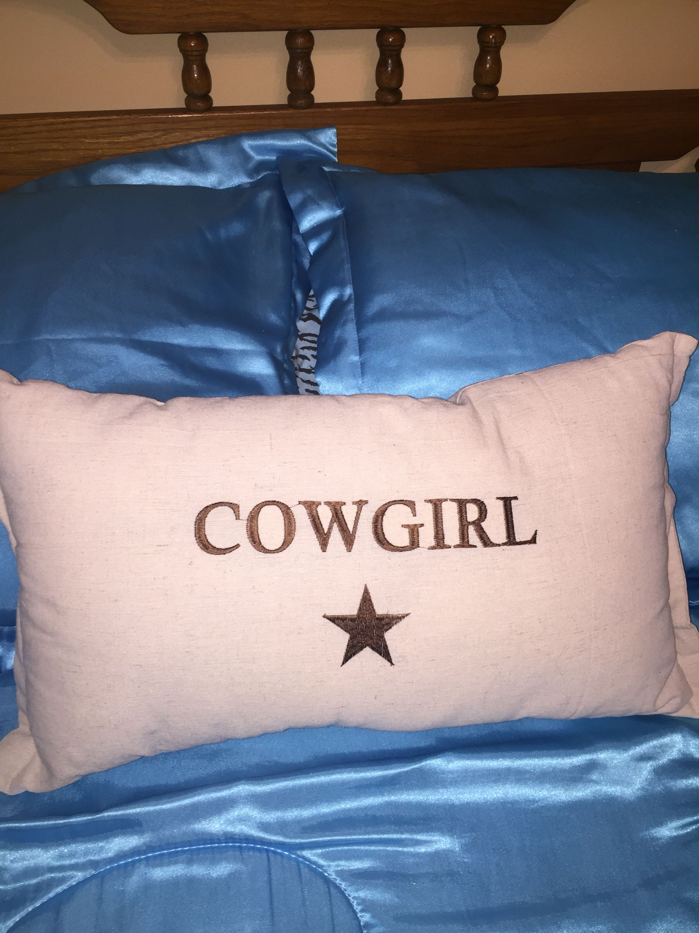 """Very nicely made oblong embroidered pillow. Oatmeal coloured with brown """"cowgirl"""". Porch pick up in White hours please"""